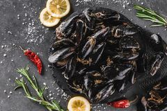 Fresh raw mussels with spices on slate stone over dark background. Seafood, top view, flat lay, copy space stock photo