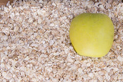 Fresh raw natural oatmeal and half green apple. Texture Stock Photography