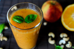 Fresh raw orange smoothie with apple, carrot and nuts on the dark background. Fresh raw orange smoothie with apple, carrot and cashew nuts on the dark background Royalty Free Stock Images