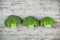 Fresh raw organic broccoli on a wooden background. Top view Stock Image