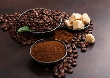 Fresh raw organic coffee beans with ground powder and cane sugar cubes with coffee trea leaf on brown background. Fresh raw organic coffee beans with ground stock photography