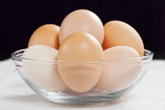 Fresh raw organic eggs in glass bowl. Fresh raw organic eggs in a glass bowl on the white cloth Stock Photography