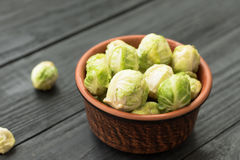 Fresh raw organic green brussel sprouts in a ceramic. Bunch of fresh Bruxelles sprouts in a cup on wooden background Royalty Free Stock Images