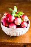 Fresh raw organic red apples in a bowl on a wooden table, selective focus. Harvesting time. Healthy and organic food option Royalty Free Stock Photography