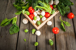 Fresh raw organic vegetables on a rustic wooden table in basket: Royalty Free Stock Images