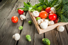 Fresh raw organic vegetables on a rustic wooden table in basket: Stock Photography