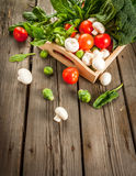 Fresh raw organic vegetables on a rustic wooden table in basket: Royalty Free Stock Photo