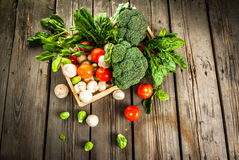Fresh raw organic vegetables on a rustic wooden table in basket:. Spinach, broccoli, Brussels sprouts, tomatoes, mushrooms, champignons Royalty Free Stock Photography