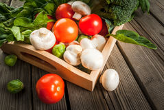 Fresh raw organic vegetables on a rustic wooden table in basket:. Spinach, broccoli, Brussels sprouts, tomatoes, mushrooms, champignons Royalty Free Stock Photo