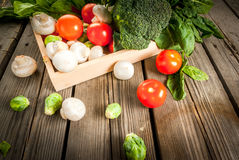 Fresh raw organic vegetables on a rustic wooden table in basket:. Spinach, broccoli, Brussels sprouts, tomatoes, mushrooms, champignons Stock Photos