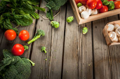 Fresh raw organic vegetables on a rustic wooden table in basket:. Spinach, broccoli, Brussels sprouts, tomatoes, mushrooms, champignons Royalty Free Stock Photos