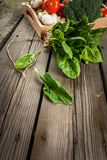 Fresh raw organic vegetables on a rustic wooden table in basket: Stock Image