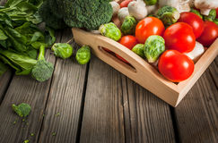 Fresh raw organic vegetables on a rustic wooden table in basket:. Spinach, broccoli, Brussels sprouts, tomatoes, mushrooms, champignons Royalty Free Stock Image