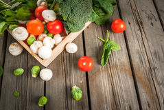 Fresh raw organic vegetables. On a rustic wooden table in basket: spinach, broccoli, Brussels sprouts, tomatoes, mushrooms, champignons. Copy space Royalty Free Stock Images