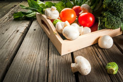 Fresh raw organic vegetables on a rustic wooden table Royalty Free Stock Photos