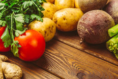 Fresh raw organic vegetables on a wooden background: tomatoes, potatoes, parsley, beets Royalty Free Stock Images