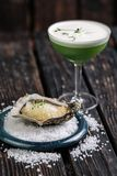 Fresh raw oyster with ice served with glass of alcohol cocktail. On dark wood background Stock Photos