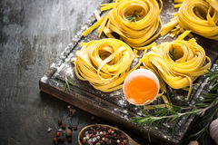 Fresh raw pasta tagliatelle and ingredients. For cooking . Italian food background Royalty Free Stock Photos