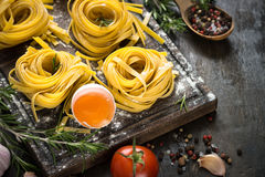 Fresh raw pasta tagliatelle and ingredients. For cooking . Italian food background Stock Image