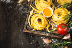 Fresh raw pasta tagliatelle and ingredients. For cooking . Italian food background Stock Photos