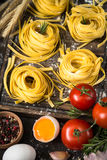 Fresh raw pasta tagliatelle and ingredients. For cooking . Italian food background Royalty Free Stock Images