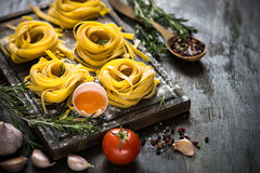 Fresh raw pasta tagliatelle and ingredients. For cooking. Italian food background Stock Image