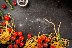 Fresh raw pasta with tomatoes. Products for preparing dinner. Fresh fresh raw homemade pasta and fresh tomatoes, cooking background, copy space top view Royalty Free Stock Image