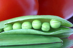 Fresh raw peas & tomatoes1015 Healthy eating. A color contrast Food & Beverage industries extreme-close-up made up of an opened pod of snow peas on a reflective Stock Photos