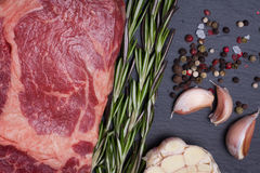 A fresh raw piece of black angus marbled meat with spices close-up on a stone dark background. Ribeye steak.  Stock Images