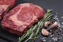 A fresh raw piece of black angus marbled meat with spices close-up on a stone dark background. Ribeye steak. Top view Royalty Free Stock Photos