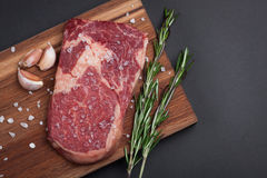 A fresh raw piece of black angus marbled meat with spices close-up on a stone dark background. Ribeye steak. Top view Royalty Free Stock Photo