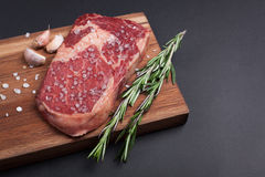 A fresh raw piece of black angus marbled meat with spices close-up on a stone dark background. Ribeye steak. Top view Royalty Free Stock Images