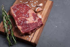 A fresh raw piece of black angus marbled meat with spices close-up on a stone dark background. Ribeye steak. Top view. Copy space Royalty Free Stock Photography