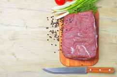 Fresh raw piece of meat lies on the kitchen blackboard. Next to onions, parsley and tomatoes and a knife with a wooden handle on a wooden table, top view Stock Photos