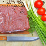 Fresh raw piece of meat lies on the kitchen blackboard. Next to onions, parsley and tomatoes and a knife with a wooden handle on a wooden table, top view Royalty Free Stock Image