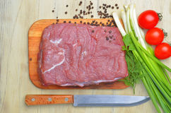 Fresh raw piece of meat lies on the kitchen blackboard. Next to onions, parsley and tomatoes and a knife with a wooden handle on a wooden table, top view Royalty Free Stock Images