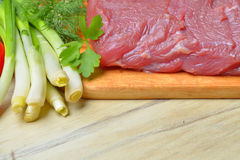 Fresh raw piece of meat lies on the kitchen blackboard. Next to onions, parsley and tomatoes on a wooden table, top view Stock Photos