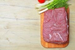 Fresh raw piece of meat lies on the kitchen blackboard. Next to onions, parsley and tomatoes on a wooden table, top view Stock Image
