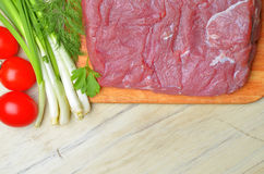 Fresh raw piece of meat lies on the kitchen blackboard. Next to onions, parsley and tomatoes on a wooden table, top view Stock Photography
