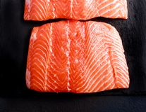Fresh, raw pieces of salmon. On board Stock Images