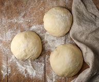 Fresh raw pizza dough. On wooden rustic table, top view Stock Photos