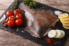 Fresh raw plaice with ingredients on a slate board. horizontal. Fresh raw plaice with ingredients on a slate board on a table close-up. horizontal Royalty Free Stock Image