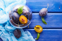 Fresh raw plums. Fresh juicy raw plums in a glass bowl at a blue wooden background Stock Photos