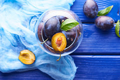 Fresh raw plums. Fresh juicy raw plums in a glass bowl at a blue wooden background Stock Image
