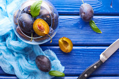 Fresh raw plums. Fresh juicy raw plums and a knife in a glass bowl at a blue wooden background Stock Photos