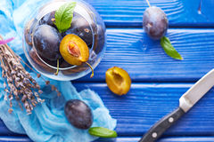 Fresh raw plums. Fresh juicy raw plums, knife and purple lavender in a glass bowl at a blue wooden background Royalty Free Stock Image