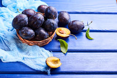 Fresh raw plums. Fresh juicy raw plums in a wicker basket at a blue wooden background Royalty Free Stock Photography