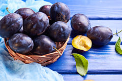 Fresh raw plums. Fresh juicy raw plums in a wicker basket at a blue wooden background. Shallow depth of field Stock Image