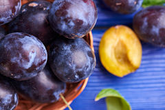 Fresh raw plums. Fresh juicy raw plums in a wicker basket at a blue wooden background. Shallow depth of field. Close view Royalty Free Stock Image