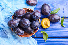 Fresh raw plums. Fresh juicy raw plums in a wicker basket at a blue wooden background. Top view Stock Image